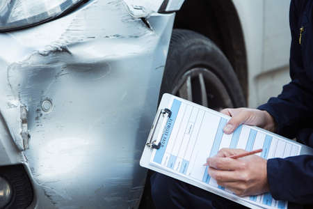 Auto Workshop Mechanic Inspecting Damage To Car And Filling In Repair Estimate Foto de archivo