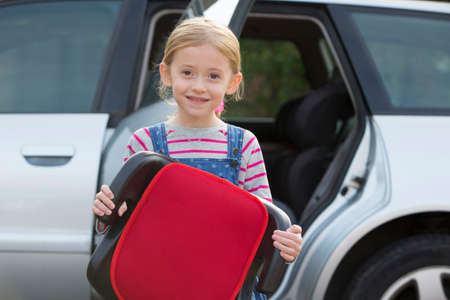 seat: Portrait Of Girl Holding Booster Seat Standing Next To Car