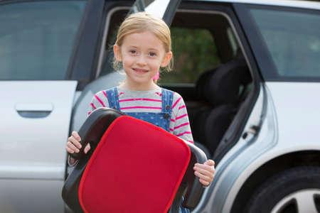 Portret Van Meisje Holding Booster Seat zich naast Auto