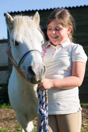 10 years old: Girl Looking After Pet Pony Stock Photo