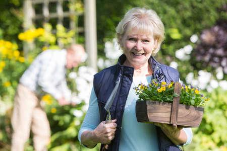 femmes souriantes: Portrait Of Senior Couple de travail dans le jardin Ensemble