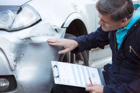 damage: Auto Workshop Mechanic Inspecting Damage To Car And Filling In Repair Estimate Stock Photo
