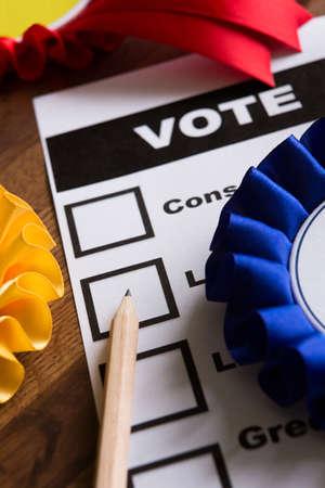 lapiz y papel: Papeleta de votación de la elección con rosetas de los partidos políticos
