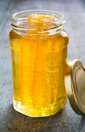 woo: Jar Of Honey With Honeycomb On Wooden Surface