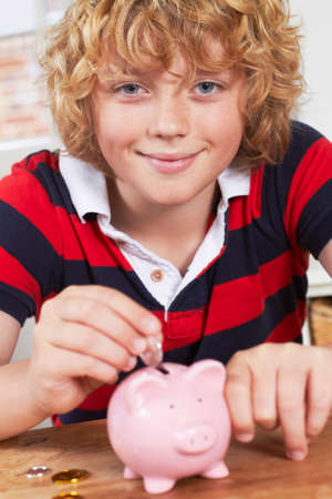 boy 12 year old: Boy Putting Coins Into Piggy Bank