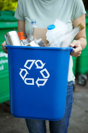 Close Up Of Woman Holding Recycling In Bin