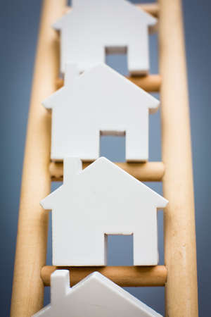 property ladder: Model Houses On Wooden Property Ladder Stock Photo