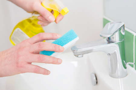 cleaning bathroom: Close Up Of Hands Cleaning Bathroom Sink Stock Photo