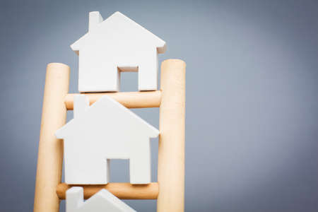 property ladder: Model Houses On Rungs Of Wooden Property Ladder