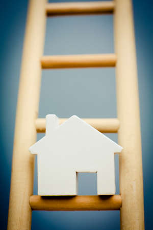 property ladder: Model House On Rung Of Wooden Property Ladder