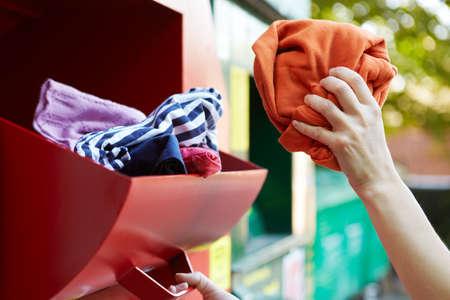 Hand Platzieren von Kleidung in Recyclingbank Standard-Bild