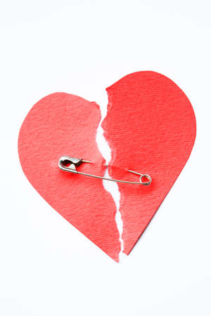 Red papier hart in tweeën gescheurd beveiligd met veiligheidsspeld op een witte achtergrond Stockfoto