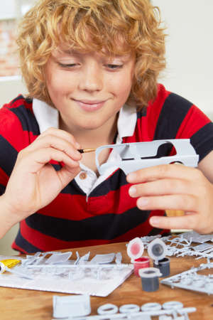 boy 12 year old: Boy Painting Model Car At Home Stock Photo