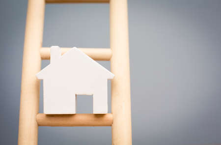 ladder: Model House On Rung Of Wooden Property Ladder