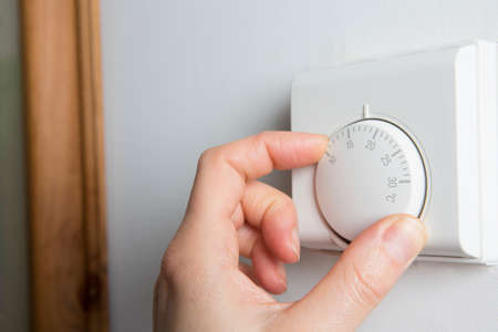 eficiencia energetica: Close Up De Mujer Mano en Calefacción central Termostato Foto de archivo