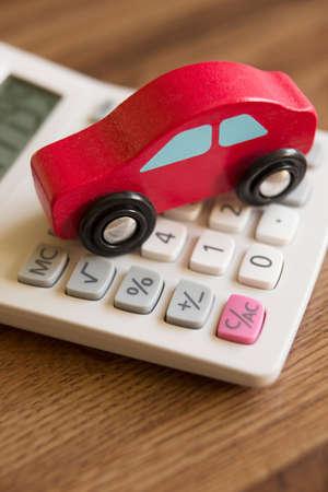 Roter Spielzeug-Auto aus Holz Auf Rechner zu veranschaulichen Kosten Auto und Motorrad