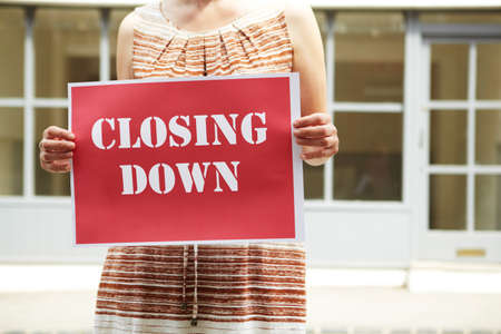 female business: Woman Standing Outside Empty Shop Holding Closing Down Sign Stock Photo