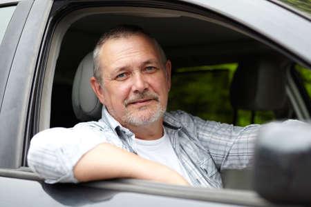 hombres maduros: Motorista maduro mirando por la ventana del coche Foto de archivo