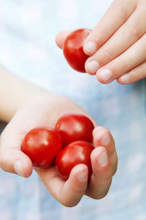 unrecognisable people: Young Girl Eating Tomatoes Stock Photo