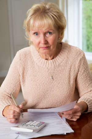 credit crunch: Concerned Senior Woman Reviewing Domestic Finances Stock Photo