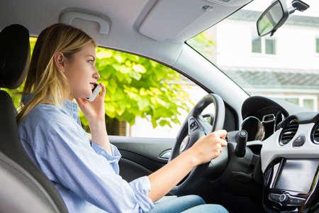 Woman In Car Talking On Mobile Phone Whilst Driving