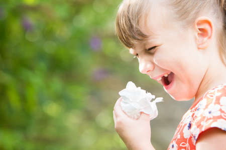 sneezing: Young Girl With Hayfever Sneezing In Garden Stock Photo