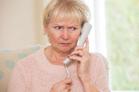 answering: Worried Senior Woman Answering Telephone At Home