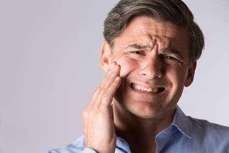 Studio Portrait Of Man Suffering With Toothache