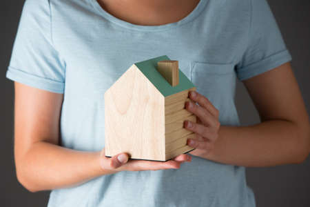 property ladder: Woman Holding Model Wooden House Stock Photo