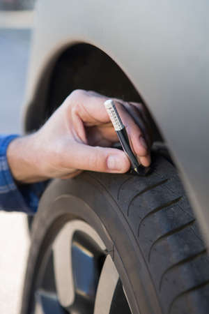 tyre tread: Close-Up Of Man Checking Tread On Car Tyre With Gauge Stock Photo