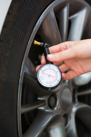 Close-Up Of Woman Checking Car Tyre Pressure With Gauge