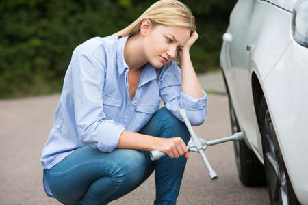 female driver: Frustrated Female Driver With Tire Iron Trying To Change Wheel Stock Photo