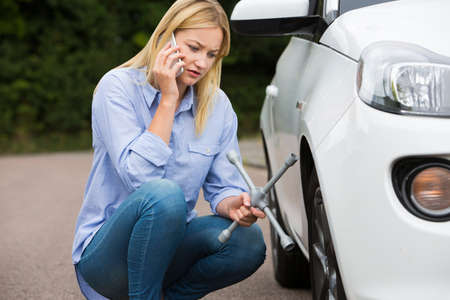 Female Motorist Phoning For Help After Breakdown