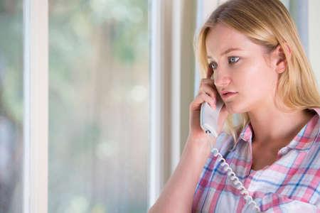Bezorgde Jonge vrouw telefoneren Helpline Stockfoto