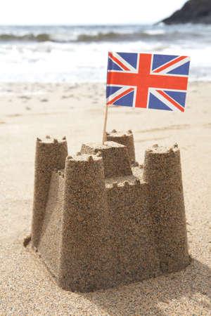 ユニオン ジャックの国旗とビーチで砂の城