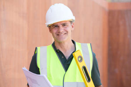 outoors: Portrait Of Construction Worker On Building Site With House Plans Stock Photo