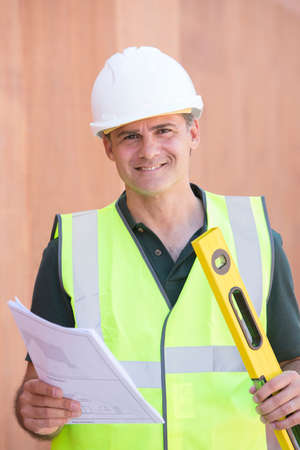 house coats: Portrait Of Construction Worker On Building Site With House Plans Stock Photo