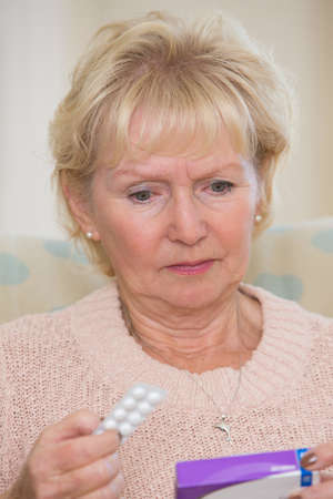 senior woman: Concerned Senior Woman Reading Information On Medicine Packet