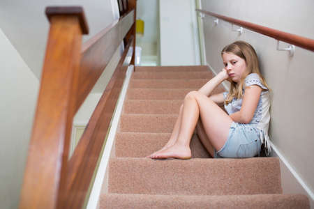 Unhappy Girl Sitting On Stairs At Home Zdjęcie Seryjne