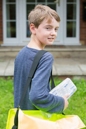 Portrait Of Teenage Boy Delivering Newspaper To House Foto de archivo