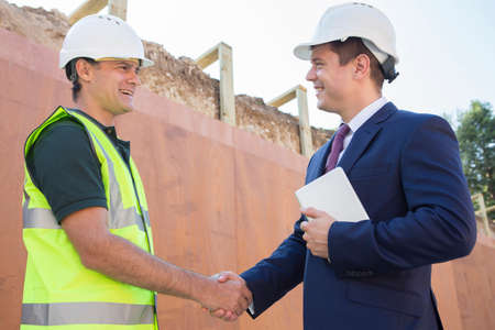 site: Businessman Shaking Hands With Builder On Construction Site Stock Photo
