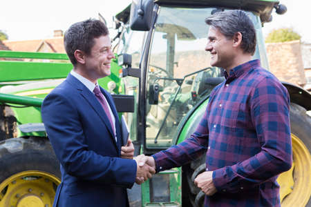 business equipment: Farmer And Businessman Shaking Hands With Tractor In Background Stock Photo
