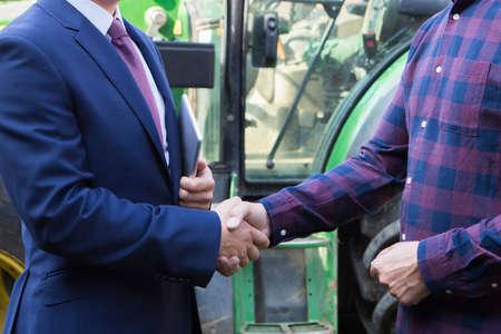 Landwirt und Geschäftsmann Händeschütteln mit Traktor im Hintergrund Standard-Bild