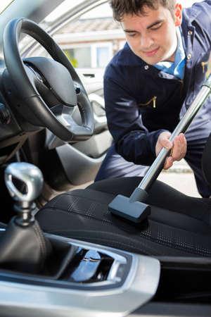 Man Hoovering Sitz des Autos Während Kfz-Reinigung