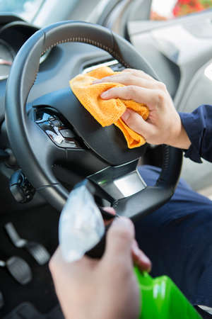 valeting: Close Of Man Cleaning Interior Of Car