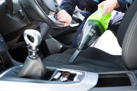 男が車内清掃中に車の座席機で掃除