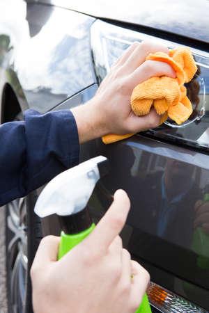 valeting: Close Up Of Hand Polishing Car Headlight Using Cloth Stock Photo
