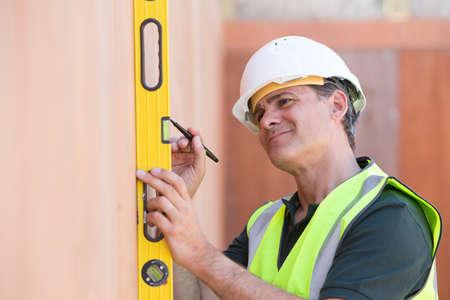 spirit level: Builder Measuring With Spirit Level