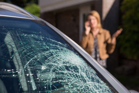 Woman Phoning For Help After Car Windshield Has Broken Stockfoto