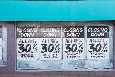 Exterior de la tienda con aviso de cierre en la ventana